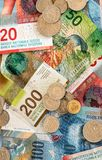 Schweizisk francpengar i mynt och färgrika räkningar arkivbilder