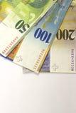 Schweizisk francsedlar av olika valörer på vit bakgrund fotografering för bildbyråer