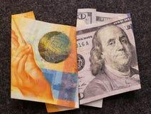 schweizisk sedel av tio franc och amerikansk sedel av 100 dollar fotografering för bildbyråer