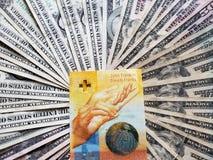 schweizisk sedel av tio franc och bakgrund med amerikanska dollarräkningar royaltyfri bild