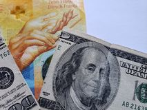 schweizisk sedel av tio franc och bruten amerikansk sedel av 100 dollar royaltyfria bilder