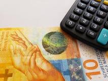 schweizisk sedel av tio franc och räknemaskin royaltyfria foton