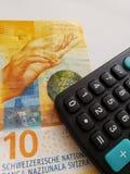 schweizisk sedel av tio franc och räknemaskin arkivfoto