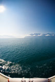 Schweizisk sjö och franska fjällängar från en färja Arkivfoto