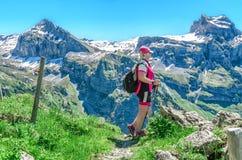 schweiziska alps En kvinna med pinnar för en gå tycker om alpin landsca Arkivfoton
