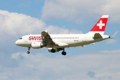 Schweiziska internationella flygbolag för flygbuss A319-112 HB-IPY i en molnig himmel, innan att landa i den Pulkovo flygplatsen Arkivfoton