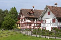 Schweiziska korsvirkes- hus i lantligt landskap Royaltyfri Bild