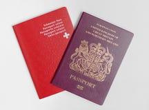 Schweiziska London/UK - Juni 21st 2019 - och UK-pass som isoleras på en vit bakgrund arkivfoto