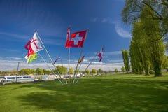 Schweiziska och distrikts-flaggor i mitten av parkerar i Kreuzlingen wi Royaltyfria Bilder