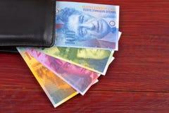 Schweiziska pengar i den svarta plånboken royaltyfri bild