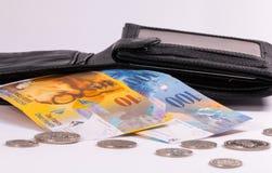Schweiziska sedlar och mynt i en plånbok royaltyfria foton