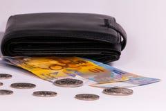 Schweiziska sedlar och mynt i a på en vit bakgrund arkivfoton