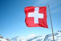 Schweiziska slag för en flagga i vinden som är hög ovanför de snöig fjällängarna Royaltyfria Bilder