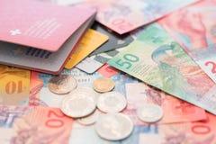 Schweiziskt pass, kreditkortar och schweizisk franc med nya 20 och 50 schweizisk franc räkningar Fotografering för Bildbyråer