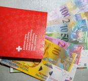Schweiziskt pass och pengar royaltyfria bilder