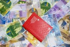 Schweiziskt pass och pengar fotografering för bildbyråer