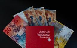 Schweiziskt pass och pengar som är nära upp på svart bakgrundsSchweiz medborgarskap arkivbilder