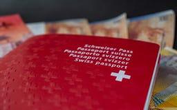 Schweiziskt pass och pengar som är nära upp på svart bakgrundsSchweiz medborgarskap royaltyfri foto