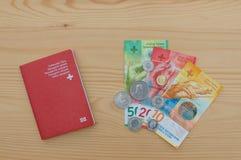 Schweiziskt pass och valuta royaltyfria bilder