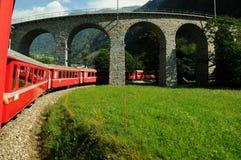 Schweiziskt rött drev Bernina som är uttrycklig på den Brusio viadukten Royaltyfria Bilder