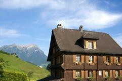 Schweiziskt trähus i fjällängberglandskap Arkivbild