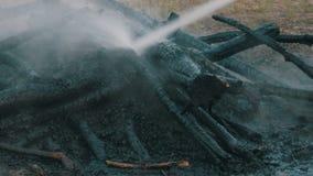Schwelende dampfende Bäume, die den Feuerwehrmann mit Wasser auslöschen Feuer im Wald stock footage