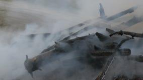 Schwelendes rauchendes Feuer, das einen Feuerwehrmann mit Wasser auslöscht Feuer im Wald stock video footage