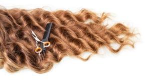 Schwemmt das gelockte Haar, Kamm und Scheren an, die auf weißem Hintergrund lokalisiert werden Stockbild