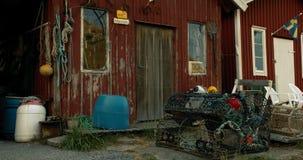 Schwenk eines alten Bootshauses mit Angelausrüstung draußen stock video footage