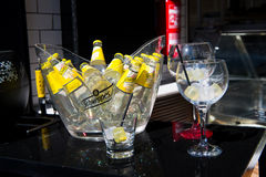 Schweppes yellow bottles in glass with ice cubes Royalty Free Stock Photos