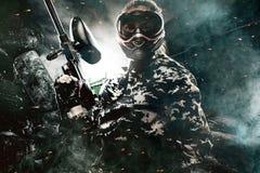 Schwer bewaffneter verdeckter Paintballsoldat auf apokalyptischem Hintergrund des Beitrags Anzeigenkonzept lizenzfreie stockbilder