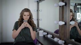 Schwer gemachtes Mädchen mit den vollen Lippen, die nahe Spiegel mit Lampen in der Umkleidekabine sitzen Sie hat langes gelocktes stock video