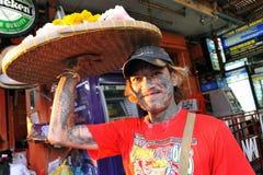 Schwer tätowierter Mann verkauft Blumen auf Straße Lizenzfreie Stockfotografie