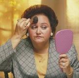 Schwere Frau, die im Spiegel beim Anwenden von makeu schaut Stockfoto
