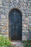 Schwere geschlossene Tür auf einer Steinwand der mittelalterlichen Festung, hergestellt befestigtes Holz Lizenzfreies Stockfoto