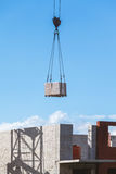 Schwere Last, die an der Baustelle des Backsteinbaus hängt Lizenzfreie Stockfotos