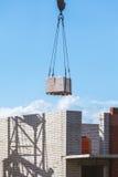 Schwere Last, die an der Baustelle des Backsteinbaus hängt Lizenzfreies Stockfoto