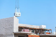 Schwere Last, die an der Baustelle des Backsteinbaus hängt Stockbild