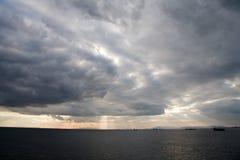 Schwere regnerische Wolken- und Sonnestrahlen. Stockbilder