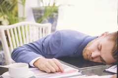 Schwerer Arbeitsbelastungsschlaf des Geschäftsmannes am Schreibtisch mit Finanzblatttaschenrechner und -kaffee Konzept für überar Stockfotos