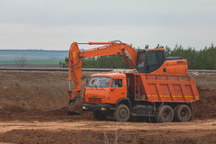 Schwerer Baggerladen-Kipper-LKW auf Straßenbau unter Feldern stockbild