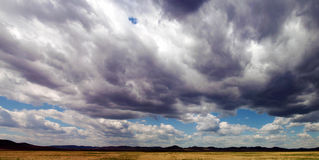 Schwerer Himmel über einem Feld Stockfotos