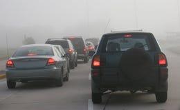 Schwerer Morgenverkehr, der über nebelige Bedingungen verhandelt Stockbild