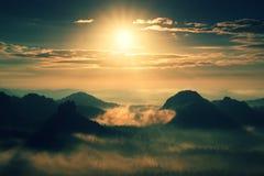 Schwerer nebelhafter Tagesanbruch Nebelhafter Sonnenaufgang im schönen hügeligen Park Spitzen von Hügeln haften heraus vom dichte Lizenzfreie Stockfotos