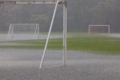 Schwerer Regenguß auf leerem, Grasfußballplatz mit der Zusammenfassung des Wassers lizenzfreies stockfoto