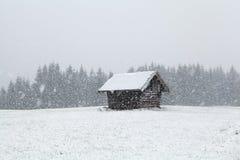 Schwerer Schneesturm über alter hölzerner Hütte Lizenzfreies Stockbild