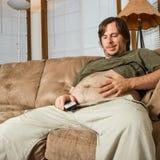 Schwerer Setmann auf der Couch seinen Magen bewundernd lizenzfreie stockfotografie