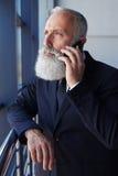 Schwerer Sir, der am Telefon beim Fenster heraus schauen spricht Stockbild