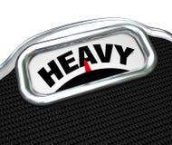 Schweres Wort auf Skala-messendem Gewicht oder Masse Lizenzfreie Stockbilder