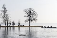 Schwerin, Germany. Silhouettes against the Sun of people, many trees, a small headland, and sportsmen in a kayak stock photography